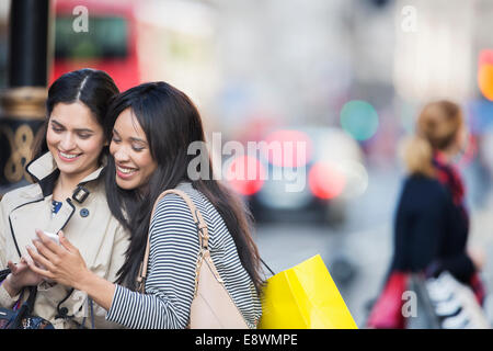 Women looking at cell phone on city street - Stock Photo