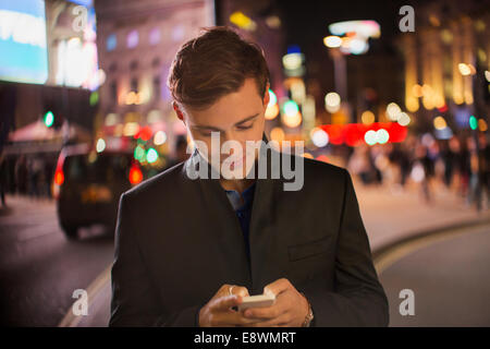 Man using cell phone on city street at night - Stock Photo