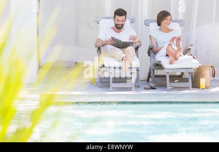 Couple relaxing in lawn chairs by swimming pool - Stock Photo