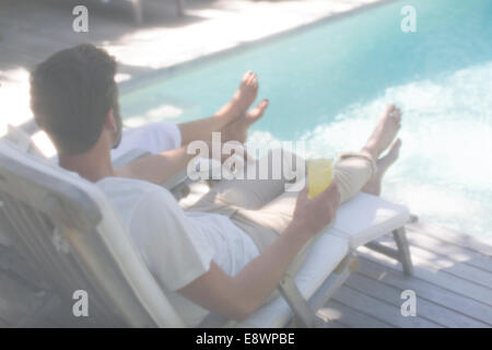 Couple relaxing together in lawn chairs by swimming pool - Stock Photo