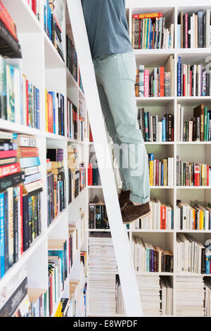 Man standing on ladder to reach books in library - Stock Photo