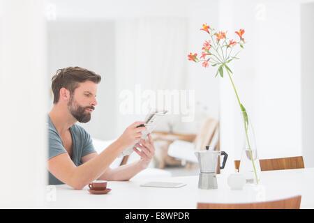 Man reading newspaper at breakfast