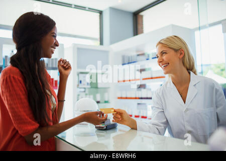 Woman paying with credit card in drugstore - Stock Photo