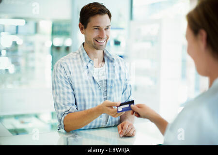 Man paying with credit card in drugstore - Stock Photo