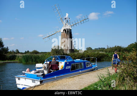 People relaxing in their motorboat on the river Ant beside Turf Fen Drainage Mill - Stock Photo