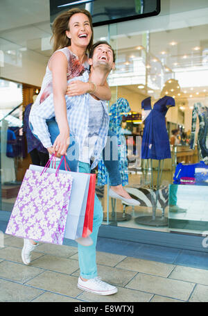 Man carrying girlfriend piggyback outside clothing store - Stock Photo