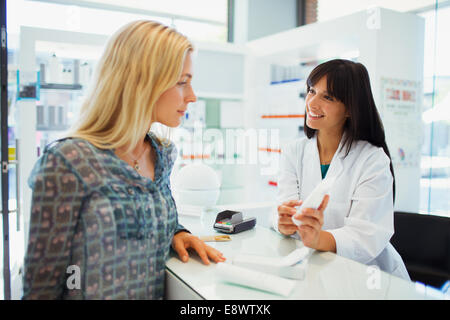 Woman discussing product with pharmacist in drugstore - Stock Photo