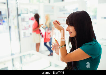 Woman trying out perfume in drugstore - Stock Photo