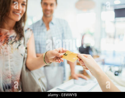 Close up of woman paying with credit card in store - Stock Photo