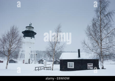 JAVRE, SWEDEN 'Smoked salmon today' sign on wooden cabin with lighthouse in background. - Stock Photo