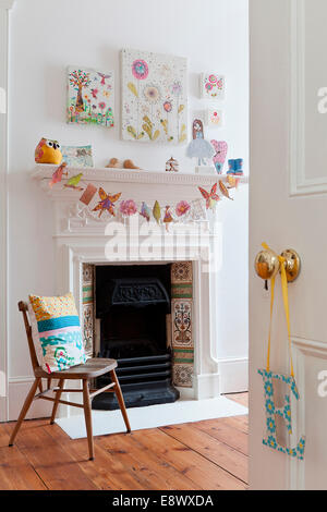 View into room with wooden chair in front of Victorian fireplace, Hove - Stock Photo