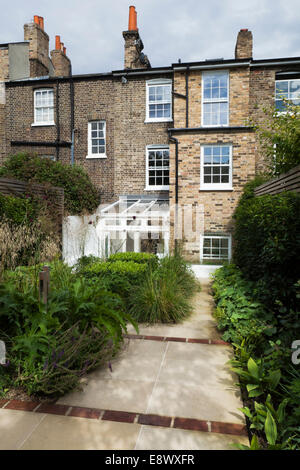 York stone paved path, interspaced with red brick, with clipped box, ornamental grasses, acanthus and alchemilla - Stock Photo