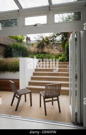 French windows open onto the lower York stone paved outside area, with benchstore and York stone steps leading up - Stock Photo