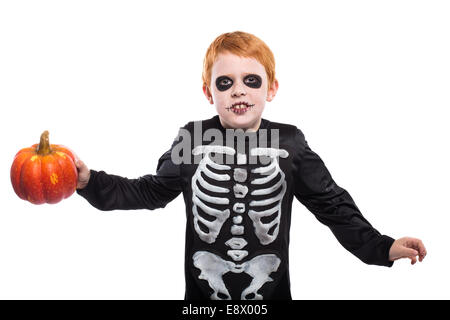 Portrait of little red haired boy wearing halloween skeleton costume and holding pumpkin - Stock Photo