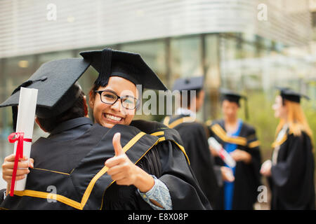 Students in cap and gown hugging - Stock Photo