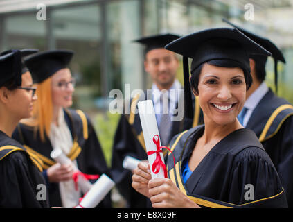 Student in cap and gown smiling with colleges - Stock Photo