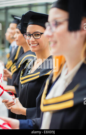 Student in cap and gown standing with colleges - Stock Photo