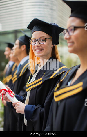 Woman in cap and gown standing with colleges - Stock Photo
