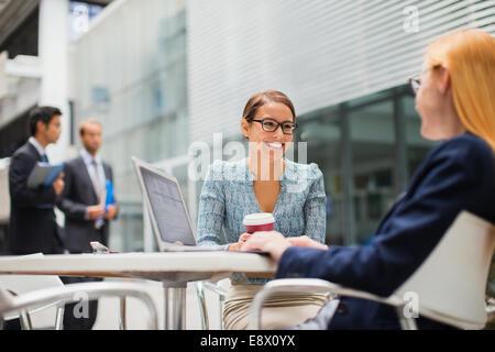 Businesswomen talking outside of office building - Stock Photo