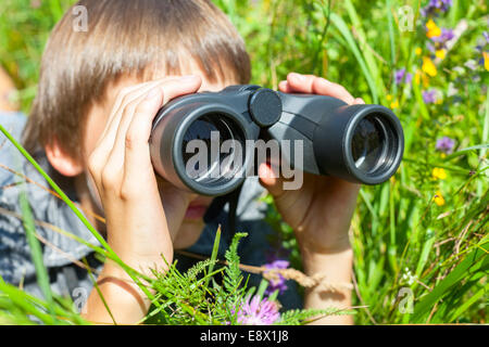 Boy hiding in grass looking through binoculars outdoor - Stock Photo