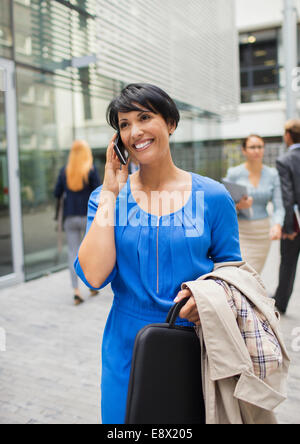 Businesswoman talking on cell phone outside of office building - Stock Photo