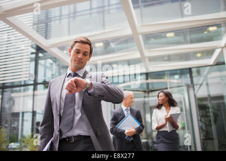 Businessman looking at watch walking out of office building - Stock Photo