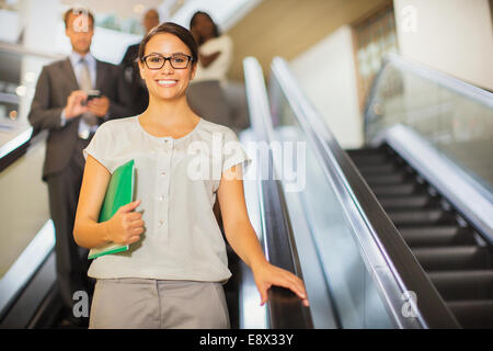 Businesswoman going down escalator in office building - Stock Photo
