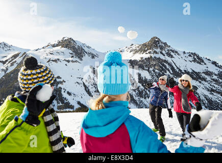 Family having a snowball fight on mountain - Stock Photo
