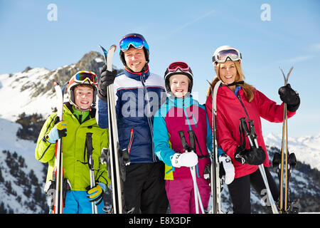 Smiling family holding ski poles on mountain - Stock Photo