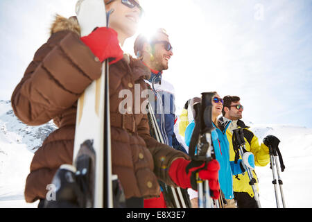 Friends standing with skis on mountain top - Stock Photo