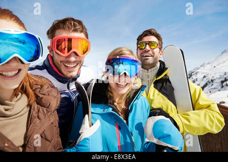 Friends carrying skis on mountain top - Stock Photo