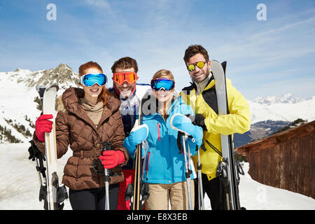 Friends on mountain top holding skis together - Stock Photo