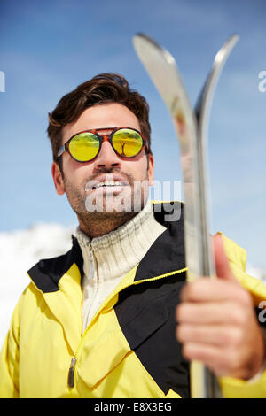 Man holding skis outdoors - Stock Photo
