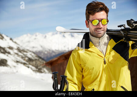 Man carrying skis on mountain top - Stock Photo