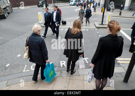 London UK. 15th October 2014. Some pedestrians cross Long Lane at traffic lights near the Barbican tube station - Stock Photo
