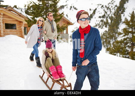 Brother pulling sister on sledge in snow - Stock Photo