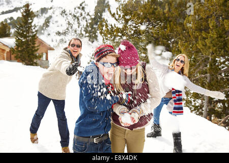Family having snowball fight together - Stock Photo