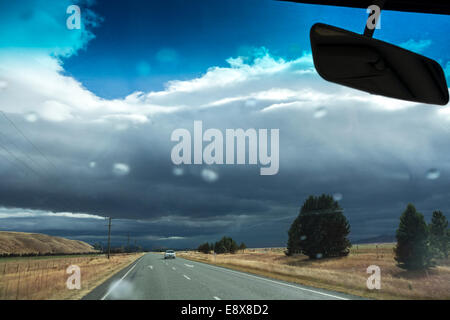 New Zealand weather can be unpredictable. Driving into a rainstorm on Highway 8 near Omarama. First rain drops on - Stock Photo
