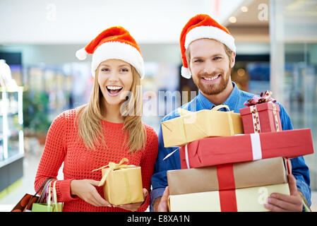 Happy couple of shoppers buying Christmas presents - Stock Photo