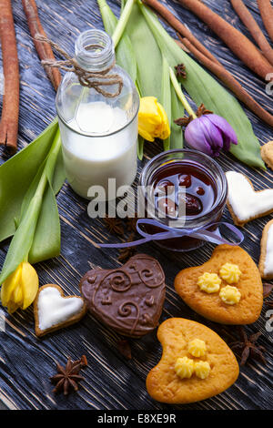 Fresh healthy milk and delicious muffins, with tulips, jam, cinnamon on a wooden background - Stock Photo