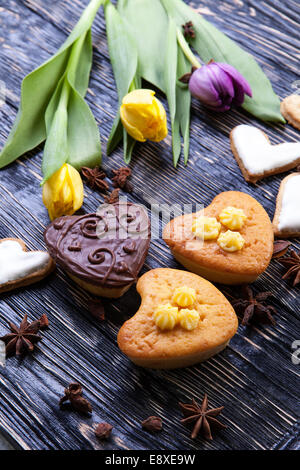 Fresh healthy and delicious muffins, with tulips on a wooden background - Stock Photo