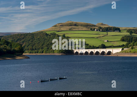 Blue summer sky over water of Ladybower Reservoir, boats moored, arches of Ashopton Viaduct & scenic hillside - - Stock Photo