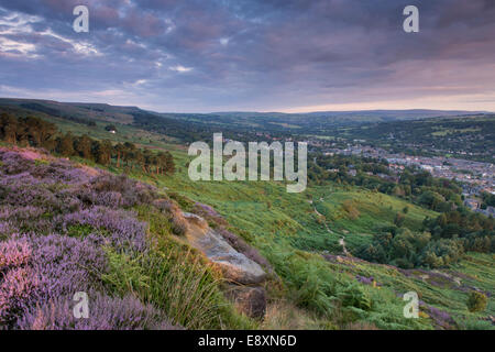 Under dramatic clouds, scenic rural morning sunrise view from high on Ilkley Moor, over town nestling in Wharfe Valley - West Yorkshire, England, UK. Stock Photo