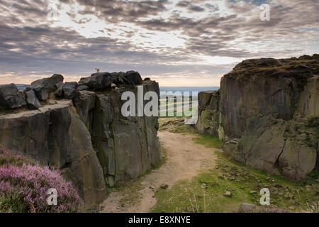 Dramatic grey cloudy sky over rocky outcrops at The Cow and Calf Rocks, Ilkley, West Yorkshire, UK - single sheep - Stock Photo