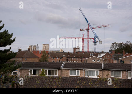 View over rooftops in York, North Yorkshire, England, UK - 3 ancient Minster towers and 3 modern cranes towering - Stock Photo