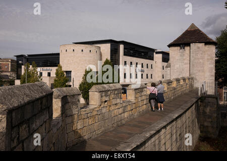 2 people on historic city walls by ancient Fishergate Postern Tower (modern architecture of Travelodge hotel beyond) - Stock Photo