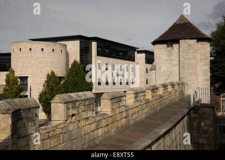 Historic city walls by ancient Fishergate Postern Tower contrast with modern architecture of Travelodge hotel beyond - Stock Photo