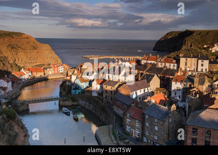 Sunny evening view of quaint sunlit seaside cottages, towering cliffs & harbour of old fishing village - Staithes, - Stock Photo