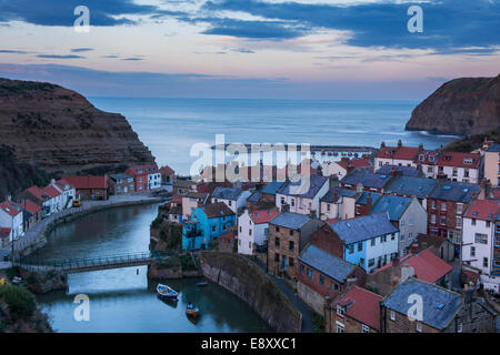 Evening view of sunset sky, quaint seaside cottages, towering cliffs & harbour of old fishing village - Staithes, - Stock Photo