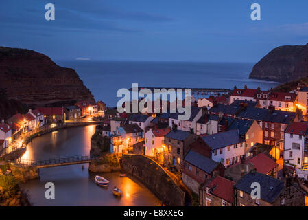 Evening view of quaint seaside cottages (lights on) towering cliffs & harbour of old fishing village - Staithes, - Stock Photo